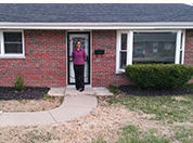 Sharon Townsend standing in front of her house