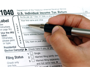 Close up of a hand filling out a 1040 EZ tax form.