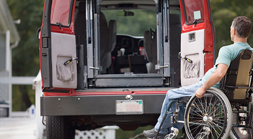 Man in wheel chair at the back of a specially adapted van.